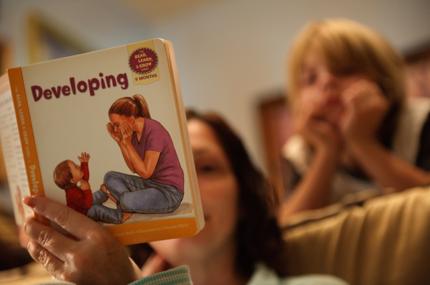 blurred photo of woman reading a book titled 'Developing' with a child in the background looking at it